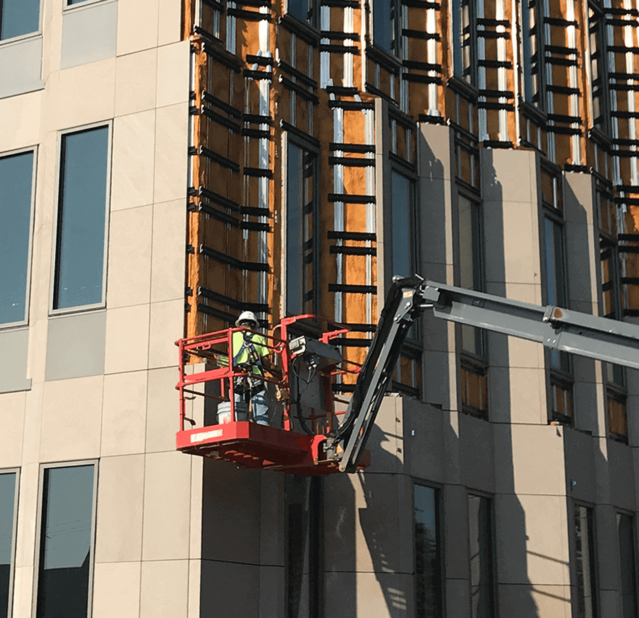 Professional installing stone panel cladding onto a building.